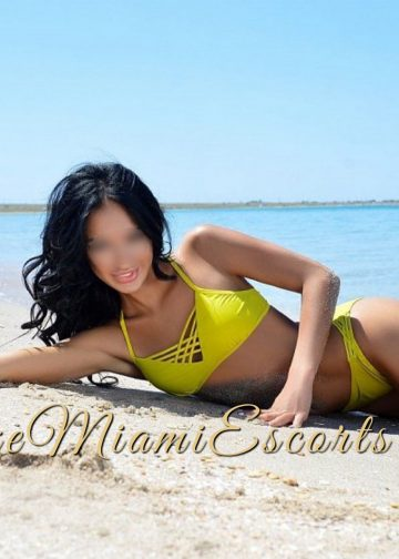 Miami escorts model Rebecca laying on her side at the beach in her yellow swim wear