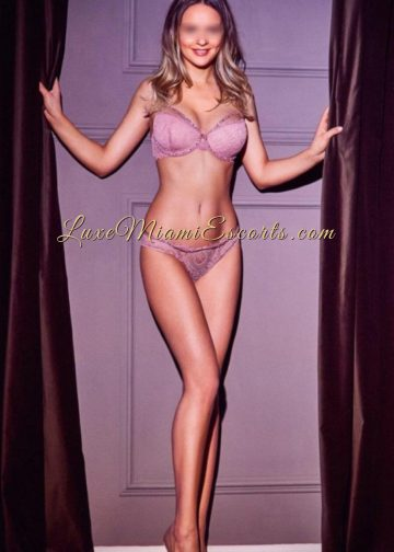 Beautiful and tall dirty blonde and busy Miami escort Sasha in her purple lingerie and heels