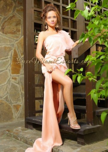 LUXE Miami Escorts presents Sofia - a gorgeous petite escort model. Photo showing Sofia standing on a stairs, wearing her pink evening dress and showing her leg