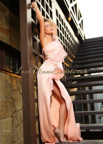 Sofia - beautiful petite escort girl in Miami posing on a stairs in her evening dress and high heels