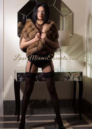 Short haired Miami brunette escort model Tiffany posing in her high heels, stockings and fur top