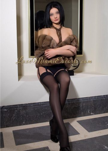 Miami escort model Tiffany sitting in black stockings, high heels and fur top