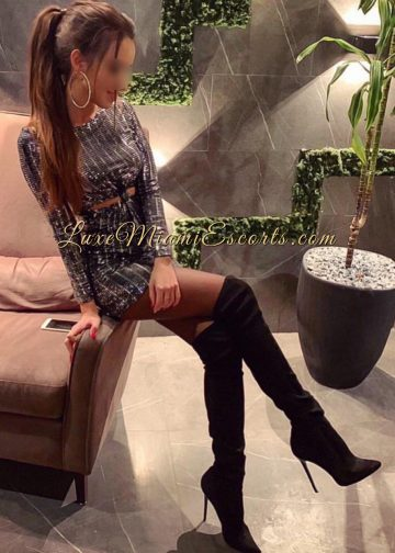 Glamorous luxe Miami escort model Veronica posing in her sexy short dress, stockings and tall high heel boots