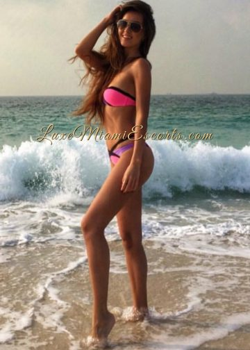 Long hair Miami brunette escort model Veronica posing at the beach in her pink swim suite