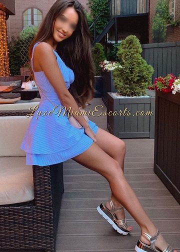 Amazing brunette escort model in Miami posing in her short blue dress and golden sandals