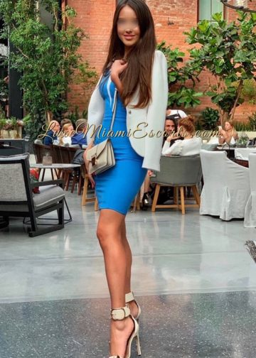 Glamorous Miami escort girl Veronica at the lounge in her sexy blue dress, beige high heels and white jacket