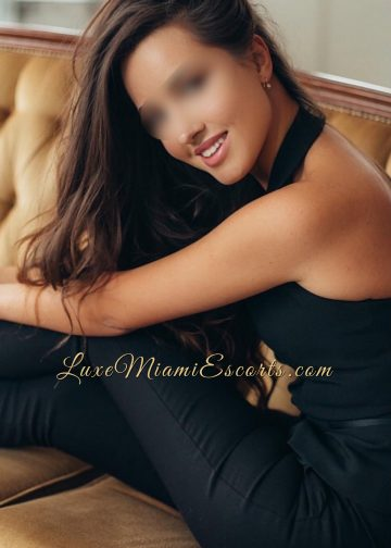 Adorable Miami escort Veronica sitting on a sofa in her sexy black pants and black top